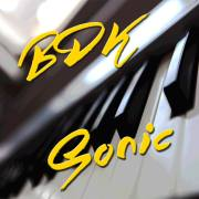 A square with a black and white piano keyboard and the inscription BDKSonic in yellow